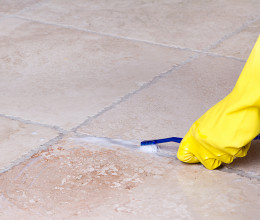 hand-with-a-yellow-glove-cleaning-grout-with-a-toothbrush