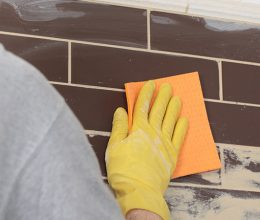 man-with-a-yellow-glove-wiping-grout-from-a-wall